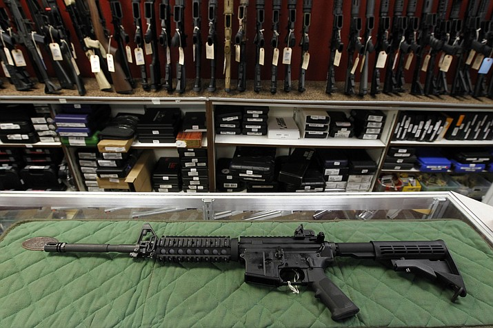 An AR-15 style rifle is displayed at the Firing-Line indoor range and gun shop Thursday, July 26, 2012, in Aurora, Colo. A new poll shows a majority of Americans favor stricter gun laws, and most believe schools and places of worship have become less safe over the last two decades, according to a poll conducted by The Associated Press-NORC Center for Public Affairs Research both before and after last week's mass shooting at two mosques in New Zealand. (Alex Brandon/AP, File)