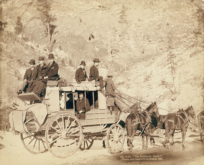 "A photo of a stagecoach, titled ""The Deadwood Coach,"" with formally dressed men sitting in and on top of the coach from around 1889. (Photo by John C. H. Grabill, Library of Congress)"
