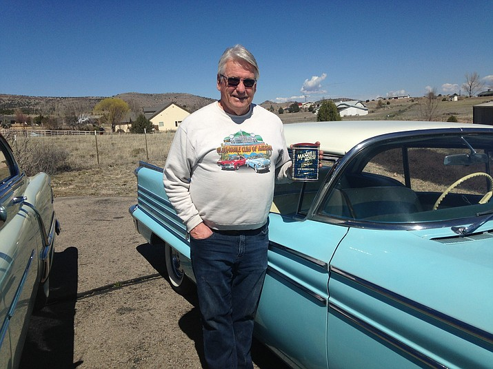 Jim Schultz poses by his 1958 Oldsmobile with his raffle coffee can. Schultz organized the ongoing event over 20 years ago. (Courtesy)