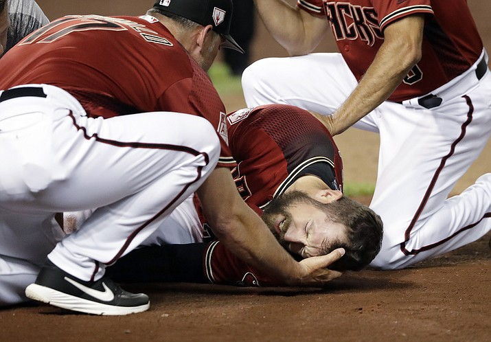 Arizona Diamondbacks' Steven Souza Jr. lies on the field and is assisted by manager Torey Lovullo, left, after getting injured while scoring against the Chicago White Sox in the fourth inning of a spring training baseball game Monday, March 25, 2019, in Phoenix. (Elaine Thompson/AP)