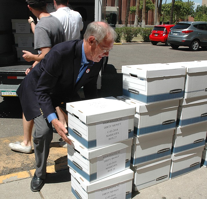 Former Attorney General Terry Goddard unloads boxes of petitions last year to put a financial disclosure requirement into the Arizona Constitution. (Howard Fischer/Capitol Media file)