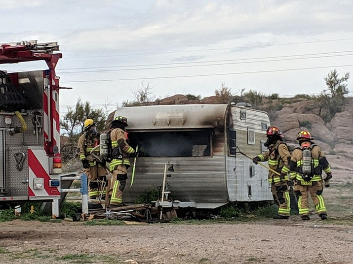 Firefighters responded to a residential fire call Tuesday, March 26, to find a camper trailer on fire. Investigators were still on scene Tuesday afternoon. (Photo by Travis Rains/Daily Miner)