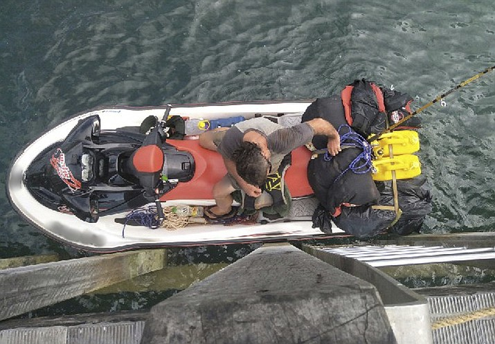 This photo released by the Australian Border Force, Wednesday, March 27, 2019, shows a wanted British man who was apprehended in the Torres Strait attempting to flee Australia on a personal watercraft. Australian police say the 57-year-old set out on Monday from the northern tip of Australia's Queensland state, carrying enough fuel to make the 140-kilometer (86-mile) trip across Torres Strait. The photo was manipulated to blur the watercraft's registration numbers. (Australian Border Force via AP)
