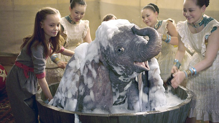 "Nico Parker, left, as Milly helps bathe the title character in Disney's live-action ""Dumbo."" Parker portrays the daughter of Colin Farrell's Holt Farrier who returns from war, minus an arm. (Disney via AP)"