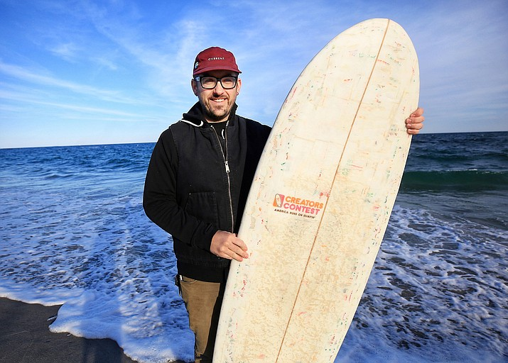 Korey Nolan of Hampton Falls, N.H., stands with the surfboard he made using hundreds of Dunkin' Donuts coffee cups and other single-use materials. He compressed the raw materials together and finished the board using bamboo, epoxy and more. (Ioanna Raptis/Portsmouth Herald via AP)