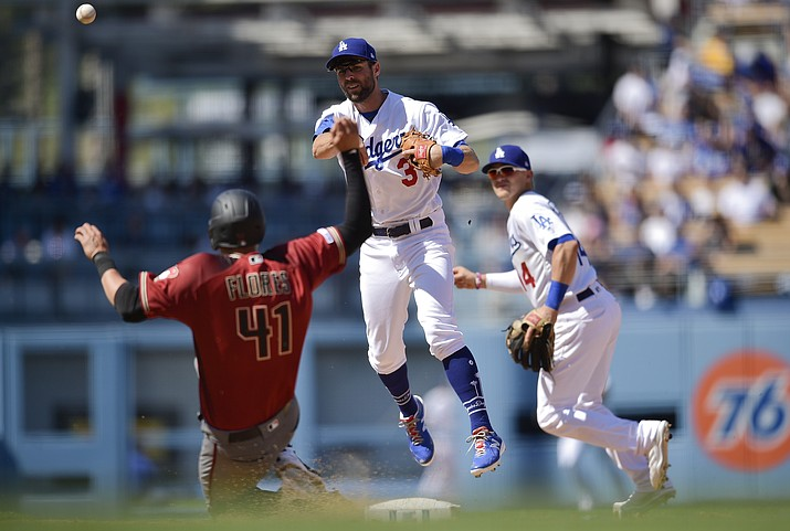 Los Angeles Dodgers shortstop Chris Taylor, center, throws to first after forcing out Arizona Diamondbacks' Wilmer Flores, left, to complete a double play during the fourth inning of a baseball game as Enrique Hernandez looks on in Los Angeles, Sunday, March 31, 2019. Ildemaro Vargas was out at first base. (Kelvin Kuo, AP)