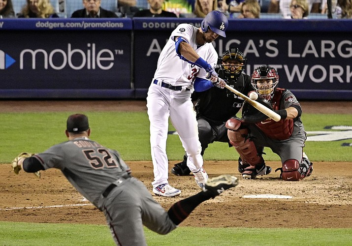 Los Angeles Dodgers' Cody Bellinger hits a solo home run off Arizona Diamondbacks starting pitcher Zack Godley during the fifth inning Saturday, March 30, 2019, in Los Angeles. (Mark J. Terrill/AP)