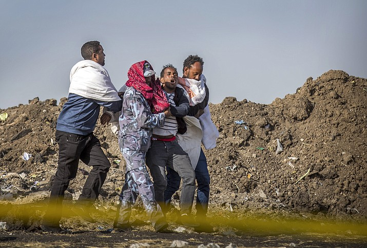 In this Wednesday March 13, 2019 file photo, a grieving relative who lost his wife in the plane crash is helped by a member of security forces and others near Bishoftu, in Ethiopia, at the scene where the Ethiopian Airlines jet crashed just after taking off from Addis Ababa on March 10, killing all 157 on board. A preliminary report finds that the crew of the Ethiopian Airlines jet that crashed last month performed all the procedures recommended by Boeing but could not control the plane. (AP Photo/Mulugeta Ayene, File)