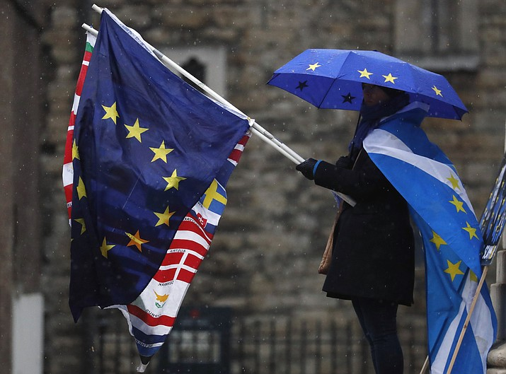 A pro EU protestor holds flags opposite the Houses of Parliament in London, Thursday, April 4, 2019. The British government and senior opposition figures were meeting Thursday in search of a new plan on how the country leaves the European Union as Prime Minister Theresa May tried to stop her shift toward compromise from splitting her Conservative Party. (Frank Augstein/AP)