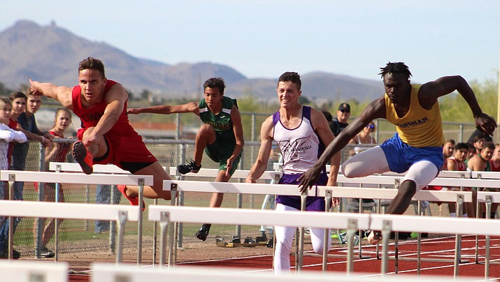 Lee Williams senior Enzo Marino, left, competes against Kingman High's Jamal Cash, right, in the 110-meter hurdles Wednesday at KHS. Cash won the event, while also taking first in the 300 hurdles. (Photo by Beau Bearden/Daily Miner)