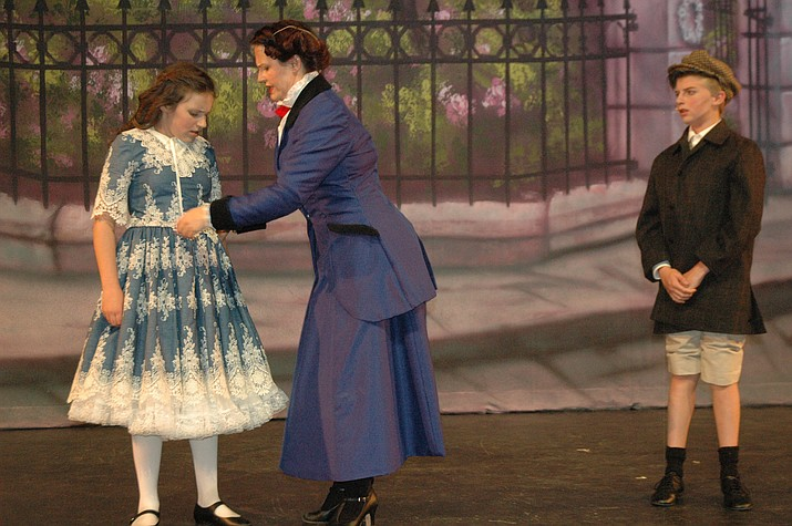 Mary Poppins, played by Joanne Cole, adjusts Jane Banks' clothing, played by Gianna Grubert while Michael Banks, played by James Howell, looks on. (Jason Wheeler/Courier)