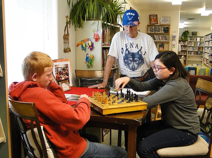 Carter Floyd, left, and Victoria Bensch, right, play chess as Jack Williamson, middle, looks on, at the Cordes Lakes Library on March 27. (Pat Williamson/Courtesy)