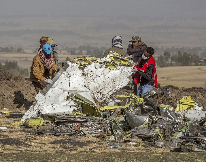 In this Monday, March 11, 2019 file photo, rescuers work at the scene of an Ethiopian Airlines flight crash near Bishoftu, or Debre Zeit, south of Addis Ababa, Ethiopia. Pilots of the Ethiopian Airlines flight encountered problems with their new Boeing jetliner from nearly the moment they roared down the runway and took off. Ethiopian authorities issued a preliminary report Thursday, April 4, 2019, on the March 10 crash. (AP Photo/Mulugeta Ayene, File)