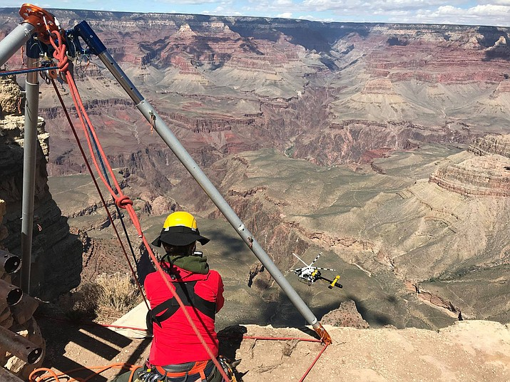 A Grand Canyon rescuer takes a break as the park helicopter moves in to long-line out the body of a 67-year-old man who fell from the edge, dropping 400 feet to his death. (Grand Canyon National Park Service)