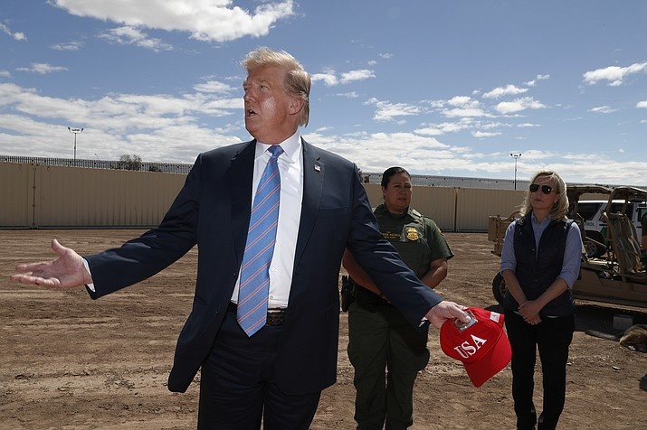 President Donald Trump visits a new section of the border wall with Mexico in Calexico, Calif., Friday April 5, 2019. Gloria Chavez with the U.S. Border Patrol, center, and Homeland Security Secretary Kirstjen Nielsen listen. (Jacquelyn Martin/AP)