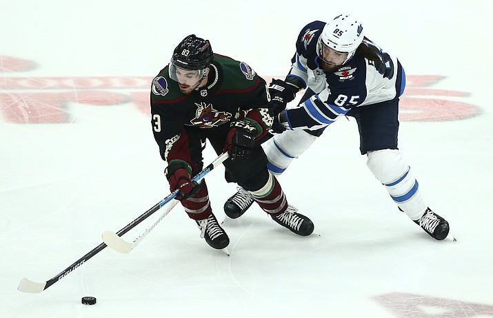 Arizona Coyotes right wing Conor Garland (83) and Winnipeg Jets left wing Mathieu Perreault (85) vie for the puck during the third period of an NHL hockey game Saturday, April 6, 2019, in Glendale, Ariz. The Jets won 4-2. (Ross D. Franklin/AP)
