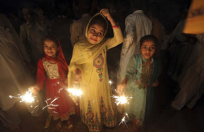Children from the Pakistani Hindu community hold fireworks during a special ceremony to celebrate Diwali festival, in Peshawar, Pakistan, Saturday, Oct. 21, 2017. Diwali, the festival of lights, is one of Hinduism's most important festivals dedicated to the worship of Lakshmi, the Hindu goddess of wealth. (AP Photo/Muhammad Sajjad)