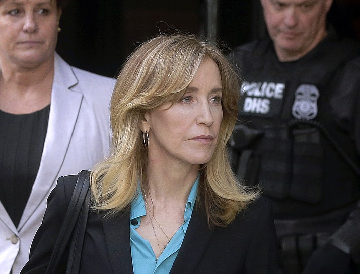 In this April 3, 2019 file photo, actress Felicity Huffman arrives at federal court in Boston to face charges in a nationwide college admissions bribery scandal. In a court filing on Monday, April 8, 2019, Huffman agreed to plead guilty in the cheating scam. (Steven Senne/AP, file)