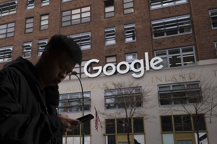 In this Dec. 17, 2018, file photo, a man using a mobile phone walks past Google offices in New York. Executives from Google and Facebook are facing Congress Tuesday, April 8, 2019, to answer questions about their role in the hate crimes and the rise of white nationalism in the U.S. (Mark Lennihan/AP, File)