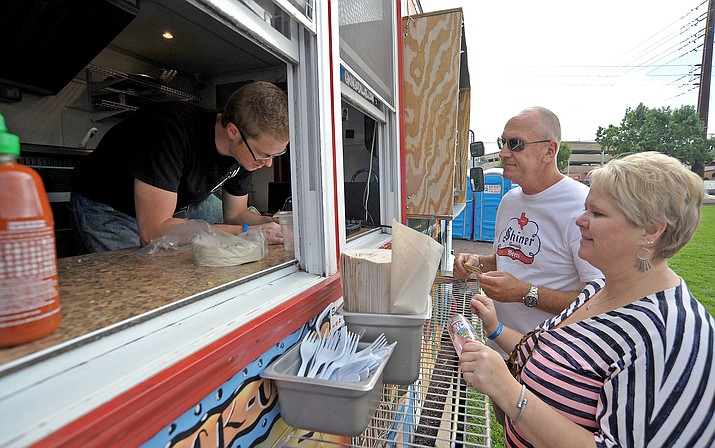 Mike Godina Co-Owner of Gringo Dillas food truck from Flagstaff takes Linda and Eric Oldham's order during the first Prescott Food Truck Festival at Mile High Middle School. (Review file photo)