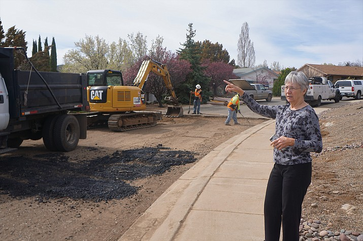 Cliff Rose resident Rita Wuehrmann explains the route of the water that ran down Marvin Gardens Lane during a major water main break in December 2018. City crews were on hand this past week patching the street. (Cindy Barks/Courier)