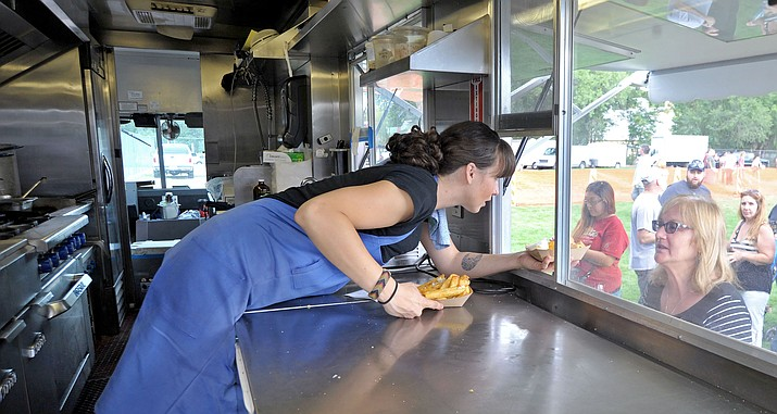 Carly Bielecki with the Frites St food truck from Phoenix hands Anne Marie Tayler a couple of orders of garlic fries during the first Prescott Food Truck Festival at Mile High Middle School. (Courier/file)