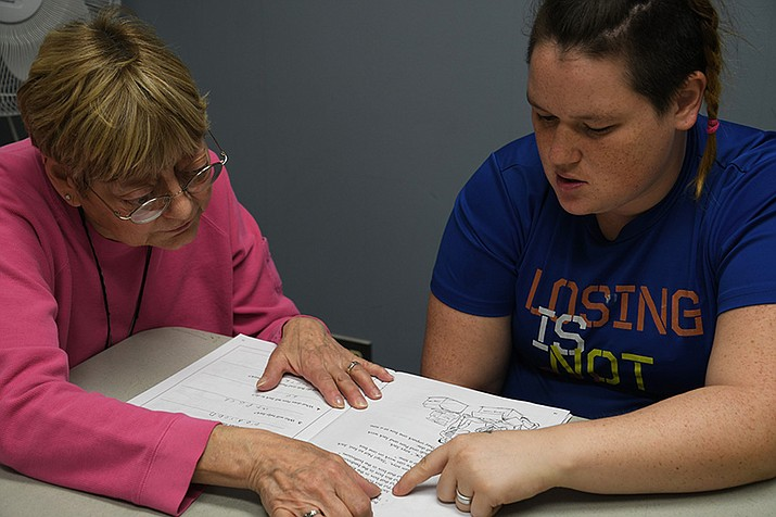 Sharon Weber, left, and Amanda Fallis go through some homework assignments during their tutoring session that they have once a week in this file photo. (Daily Miner file photo)