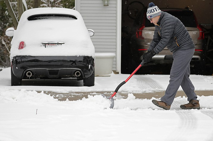 Miguel Leiva shovels his driveway along North Racine Street during a spring snow storm Thursday, April 11, 2019, in Appleton, Wis. The second major snowstorm in the region in a month left behind hazardous road conditions, wintertime temperatures and snarled traffic in Colorado and Wyoming.(Dan Powers/The Post-Crescent via AP)