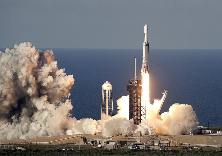 A SpaceX Falcon Heavy rocket carrying a communication satellite lifts off from pad 39A at the Kennedy Space Center in Cape Canaveral, Fla., Thursday, April 11, 2019. (AP Photo/John Raoux)