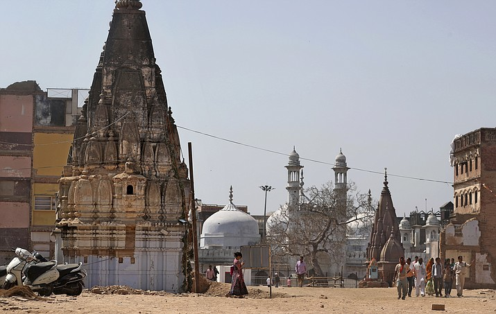 A 17th-century Gyanvapi mosque, the white structure sandwiched between Hindu tem ples, is seen in the background March 19, 2019, as Hindu devotees walk at the site of a proposed grand promenade connecting the sacred Ganges River with a centuries-old temple dedicated to Lord Shiva, in Varanasi, India. (Altaf Qadri/AP)
