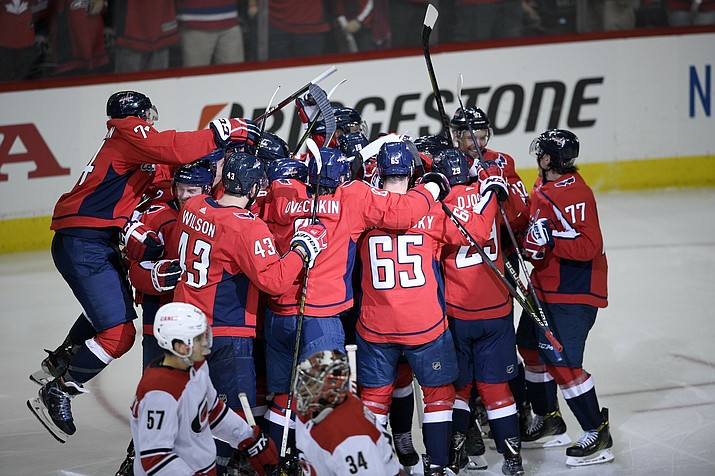 The Washington Capitals celebrate after overtime of Game 2 of an NHL first-round playoff series as Carolina Hurricanes defenseman Trevor van Riemsdyk (57) and goaltender Petr Mrazek (34) skate by, Saturday, April 13, 2019, in Washington. The Capitals won 4-3 in overtime. (Nick Wass/AP)
