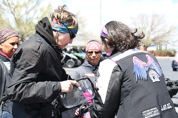 Connie Sadler, left, of the SinSitySisters Las Vegas chapter of Women in the Wind explains the rules of the baton pass to E. Kimberly of San Diego while members of the Mohave County Cactus Cuties watch. This baton pass was a national ripple relay that is running in parallel with the Women Riders World Relay. (Photo by Vanessa Espinoza/Daily Miner)