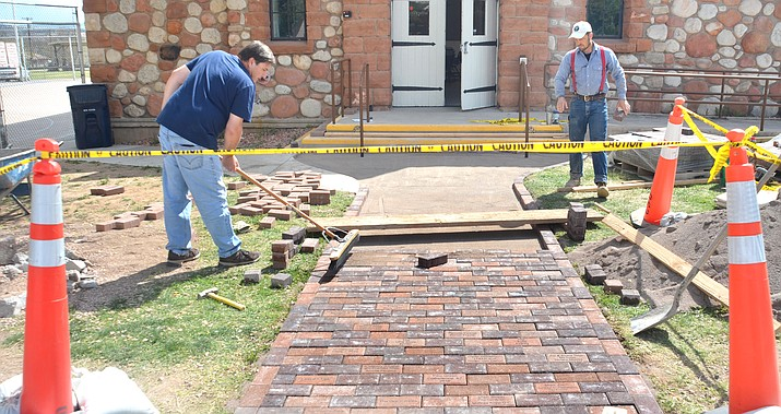 Cottonwood Mayor Tim Elinski, right,  and City Council Member and Historic Preservation Commissioner Michael Mathews install the first batch of the Commemorative Memorial Bricks at the Cottonwood Community Club House Friday.  People can buy bricks to be placed in the front of walkway of the club house to raise funds for the ongoing preservation of the facility. VVN/Vyto Starinskas