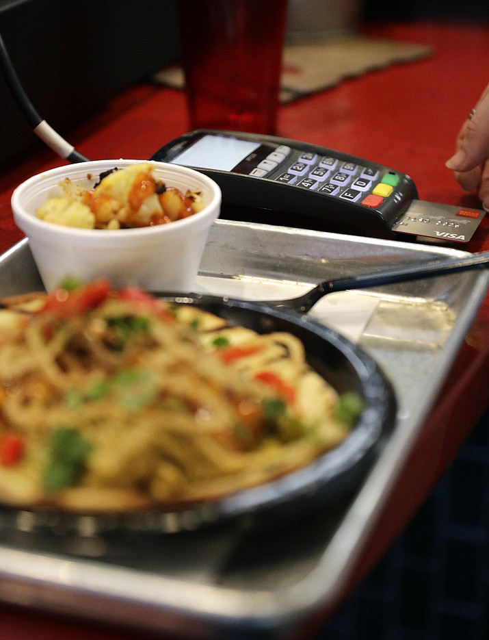 In this April 10, 2018, file photo, a customer uses a credit card machine to pay for food at Peli Peli Kitchen in Houston. Owner Thomas Nguyen had a change of heart after transitioning one of his three Peli Peli South African fine dining restaurants and his Peli Peli Kitchen fast casual location to a no-cash policy. (David J. Phillip/AP, File)