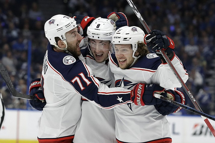 Columbus Blue Jackets defenseman Zach Werenski (8) celebrates his goal against the Tampa Bay Lightning with left wing Nick Foligno (71) and left wing Artemi Panarin (9) during the first period of Game 2 of an NHL Eastern Conference first-round hockey playoff series Friday, April 12, 2019, in Tampa, Fla. (Chris O'Meara/AP)