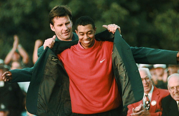 In this April 13, 1997, file photo, Masters champion Tiger Woods receives his Green Jacket from last year's winner Nick Faldo, rear, at the Augusta National Golf Club in Augusta, Ga. Woods completes an amazing journey by winning the 2019 Masters, overcoming 11 years of personal foibles and professional pain that seemed likely to be his lasting legacy. (Dave Martin/AP, File)