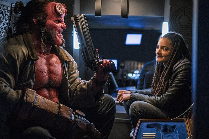 """This image released by Lionsgate shows David Harbour, left, and Sasha Lane in a scene from """"Hellboy."""" (Mark Rogers/Lionsgate)"""