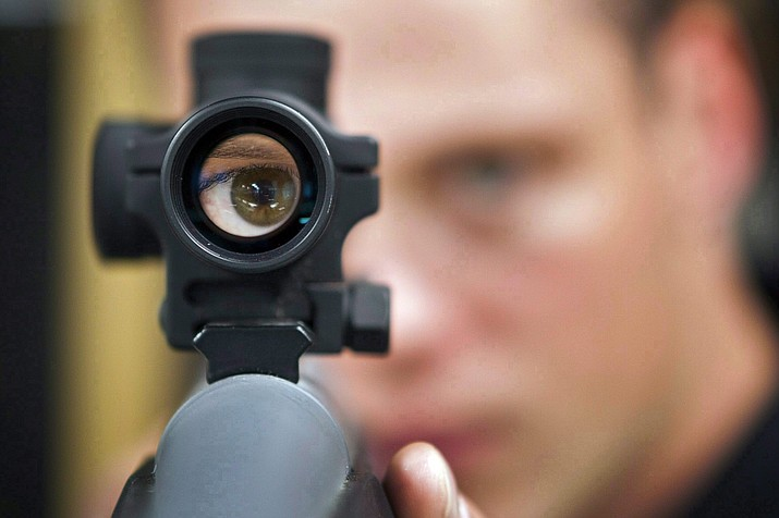 In this Sept. 15, 2010 file photo, an employee looks through the scope of long gun at a gun store in Calgary, Alberta, Canada. When Canada first sought to restrict gun access in the 1990s, the National Rifle Association threatened a boycott by U.S. hunters spending tourism dollars in the country. (Jeff McIntosh/The Canadian Press via AP)