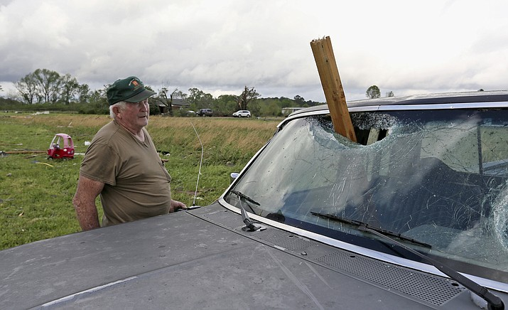A man looks at a piece of wood that was blown through the windshield of his daughters truck in Hamilton, Miss., after a storm moved through the area Sunday, April 14, 2019. (Jim Lytle/AP)