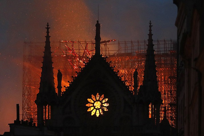 Flames and smoke rise from Notre Dame cathedral as it burns in Paris, Monday, April 15, 2019. Massive plumes of yellow brown smoke is filling the air above Notre Dame Cathedral and ash is falling on tourists and others around the island that marks the center of Paris. (Thibault Camus)