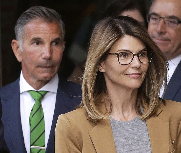 In this April 3, 2019 file photo, actress Lori Loughlin, front, and husband, clothing designer Mossimo Giannulli, left, depart federal court in Boston after facing charges in a nationwide college admissions bribery scandal. Loughlin and her husband Giannulli said in court documents Monday, April 15, 2019, that they are pleading not guilty to charges that they took part in a sweeping college admissions bribery scam. (Steven Senne/AP, File)