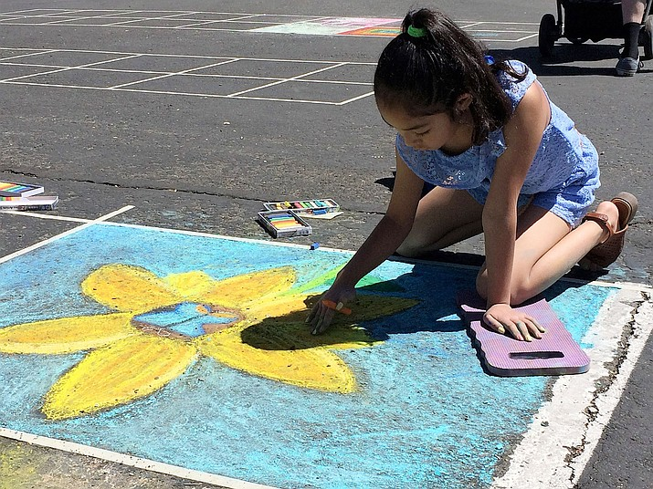 Carlene Smith, 9, of Prescott, works on a sunflower at the 11th annual Chalk It Up! event, April 13-14, in the parking lot of the National Bank of Arizona, 201 N. Montezuma St. (Sue Tone/Courier)