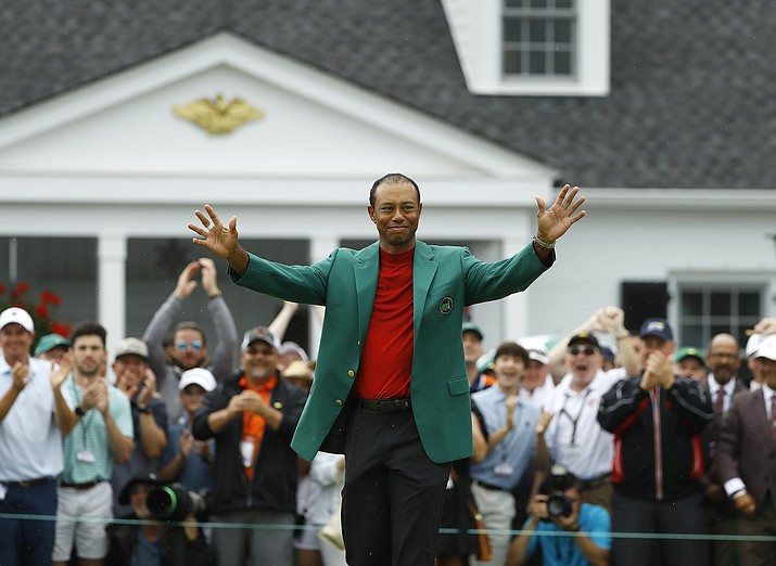 Tiger Woods smiles as he wears his green jacket after winning the Masters golf tournament Sunday, April 14, 2019, in Augusta, Ga. (Matt Slocum/AP)