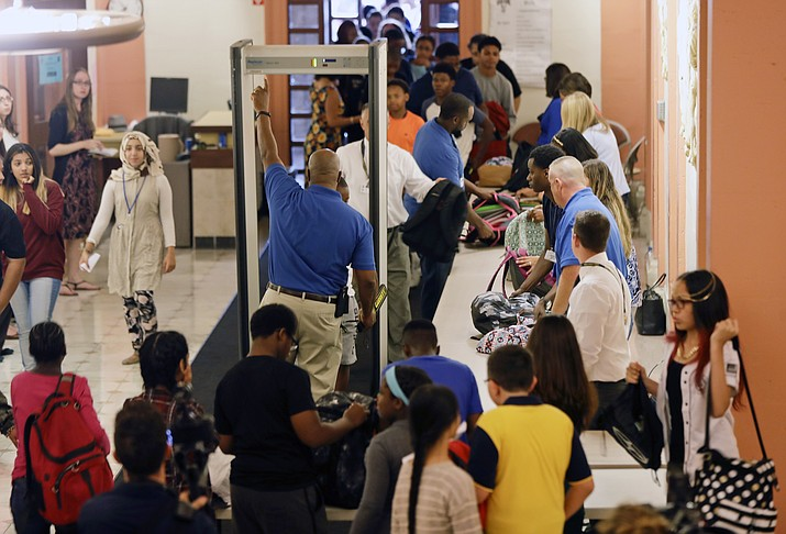 In this Sept. 6, 2016, file photo, students at William Hackett Middle School have their bags checked and pass through metal detectors on the first day of school in Albany, N.Y. Twenty years after the Columbine High School shooting made practicing for armed intruders as routine as fire drills, many parents have only tepid confidence in the ability of schools to stop a gunman, according to a new poll by The Associated Press-NORC Center for Public Affairs Research. (Mike Groll/AP, File)