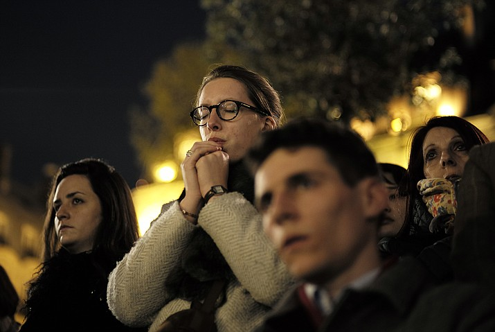 People attend a vigil in Paris, Tuesday April 16, 2019. Firefighters declared success Tuesday in a more than 12-hour battle to extinguish an inferno engulfing Paris' iconic Notre Dame cathedral that claimed its spire and roof, but spared its bell towers and the purported Crown of Christ. (Kamil Zihnioglu/AP)