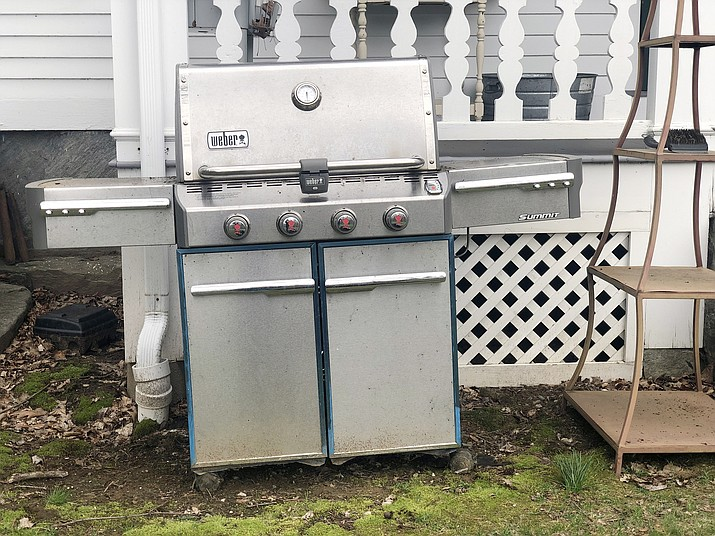 A grill sits outside a home in New Milford, Conn., on April 14, 2019, in need of some upkeep after sitting unused during the winter months. (Katie Workman via AP)