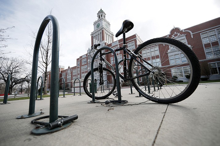 "A lone bicycle stands in the rack outside East High School, Wednesday, April 17, 2019, in Denver. Denver-area public schools closed Wednesday as the FBI hunted for an armed young Florida woman who was allegedly ""infatuated"" with Columbine and threatened violence just days ahead of the 20th anniversary of the attack. (David Zalubowski/AP)"
