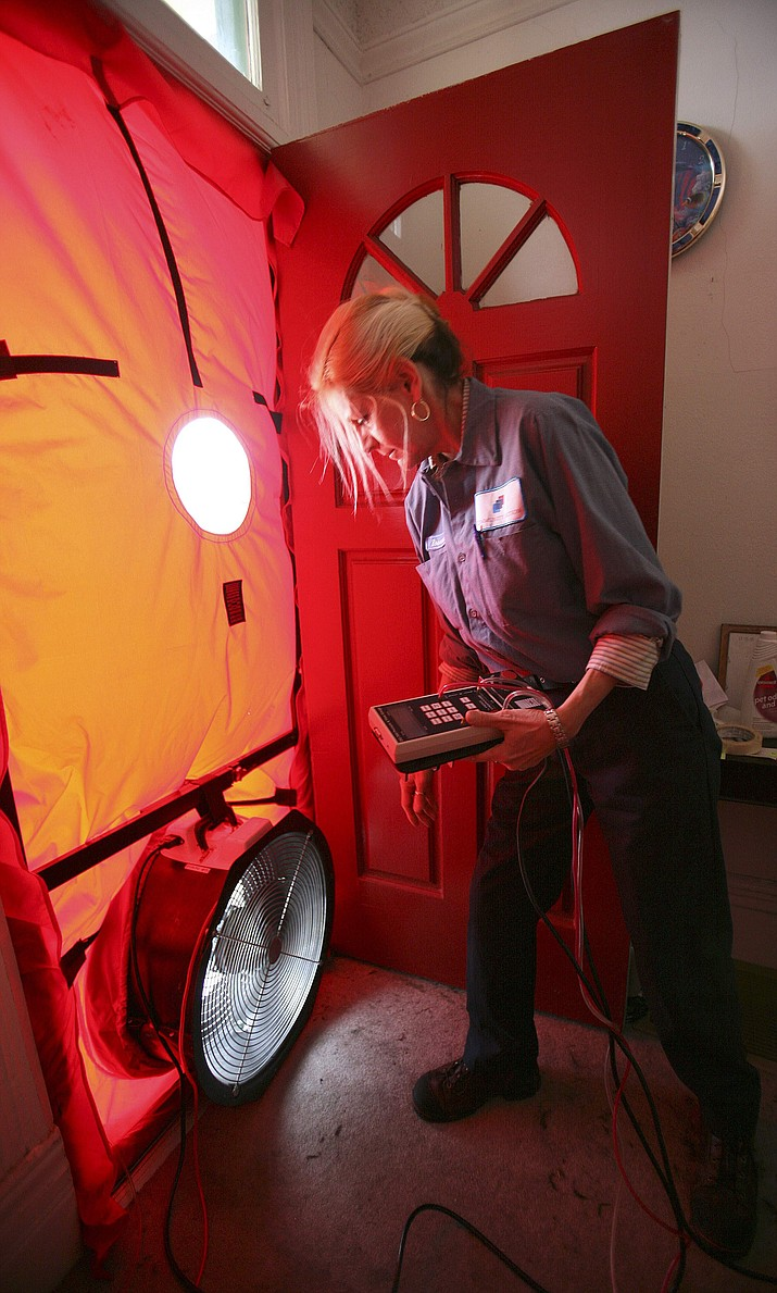 Roseann Mitchell, of the Community Action Agency, checks airflow readings as part of a blower door test assessment Feb. 26, 2010, in San Francisco. (Ben Margot/AP, file)