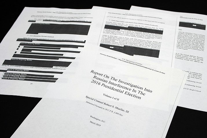 Four pages of the Mueller Report lay on a witness table in the House Intelligence Committee hearing room on Capitol Hill, in Washington, Thursday, April 18, 2019. (Cliff Owen/AP)
