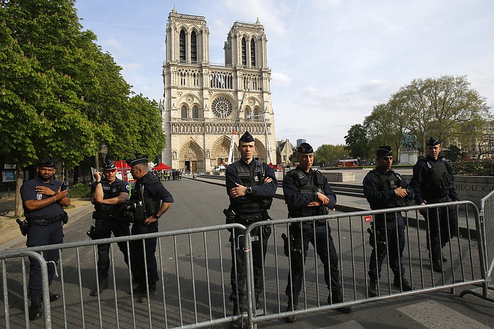 Police officer stand behind the security barriers in front of Notre Dame cathedral Thursday, April 18, 2019 in Paris. France paid a daylong tribute Thursday to the Paris firefighters who saved Notre Dame Cathedral from collapse, while construction workers rushed to secure an area above one of the church's famed rose-shaped windows and other vulnerable sections of the fire-damaged landmark. (Michel Euler/AP, pool)